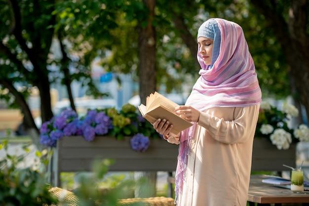 Mujer joven casual en hijab mirando a través del libro mientras pasa tiempo en el parque o terraza