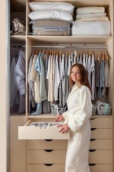Mujer joven caucásica ama de casa en una bata de felpa blanca con contenedor con ropa interior, calcetines y calzoncillos. almacenamiento de ropa.