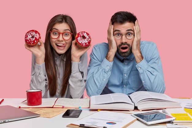 Mujer joven caucásica positiva come sabrosas rosquillas rojas, usa gafas, frustrado desconcertado chico sin afeitar en camisa formal se siente harto del trabajo