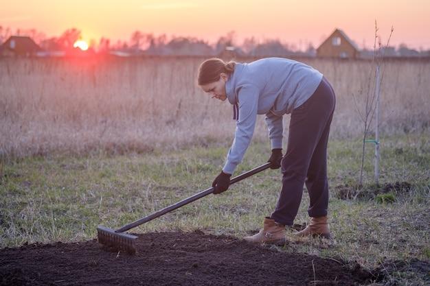 Mujer joven cava la tierra en un jardín. preparando la tierra para sembrar semillas