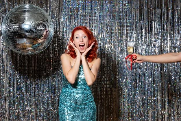 Mujer joven celebrando el año nuevo en la fiesta y tomando champán en cortinas brillantes
