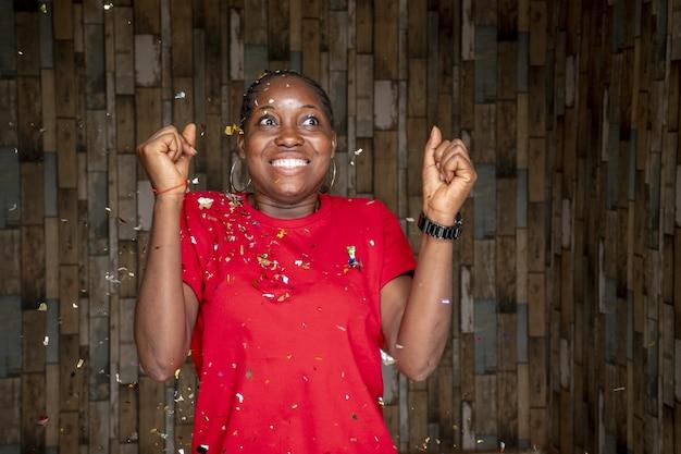 Mujer joven celebrando con confeti flotando alrededor