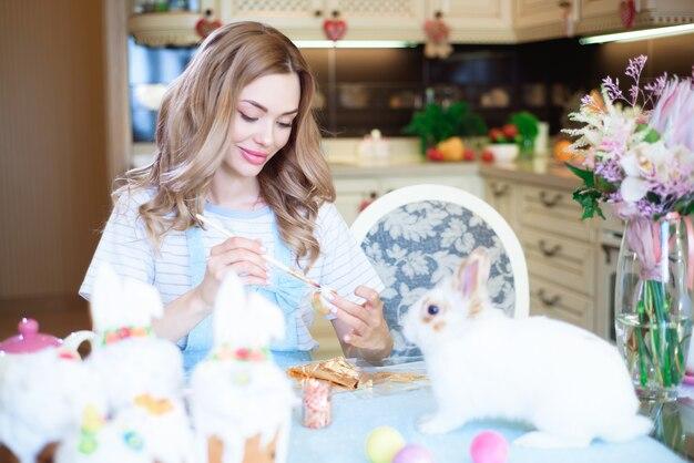 Mujer joven celebrando la pascua, pintando huevos con pincel.
