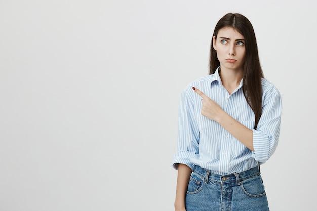 Mujer joven celosa o triste apuntando hacia la izquierda, haciendo pucheros triste