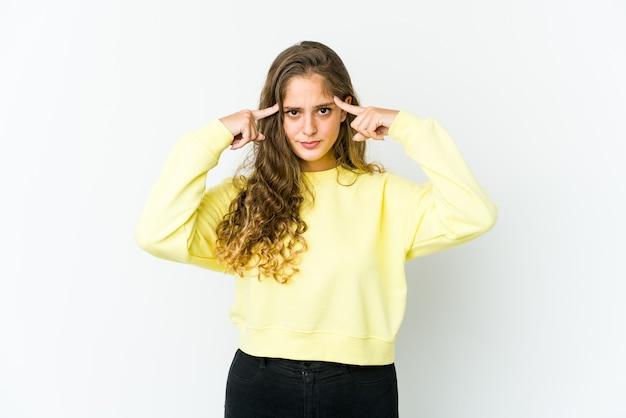 Mujer joven centrada en una tarea, manteniendo los dedos índice apuntando hacia la cabeza