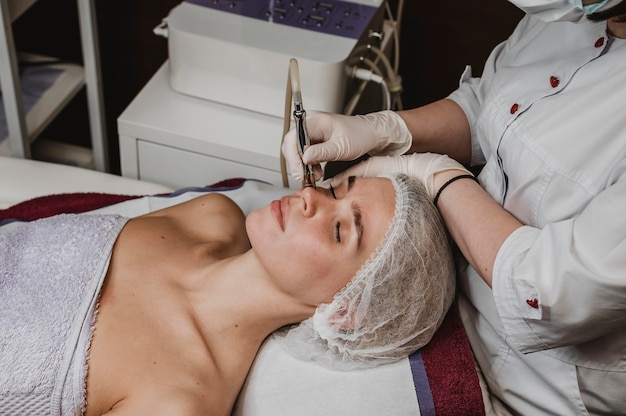 Mujer joven en el centro de bienestar con un tratamiento cosmético