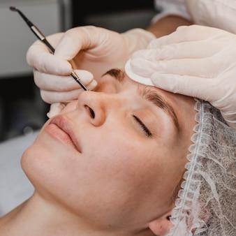 Mujer joven en el centro de bienestar durante un tratamiento para la piel