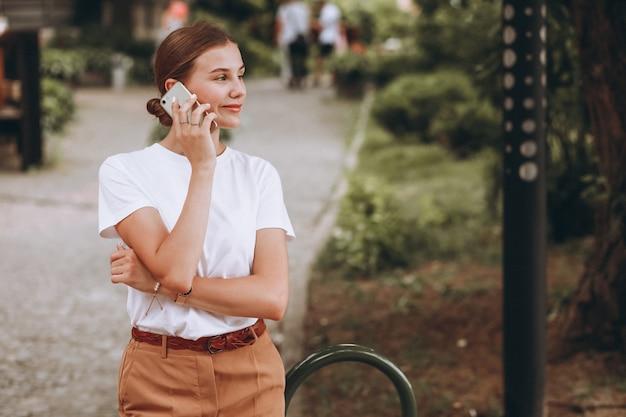Mujer joven en el centro de la ciudad hablando por teléfono