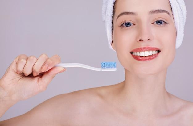 Una mujer joven con un cepillo de dientes sonríe ampliamente. de cerca.