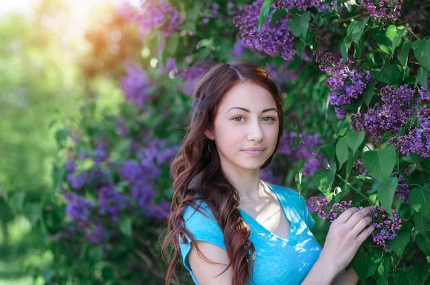 Mujer joven cerca del arbusto lila