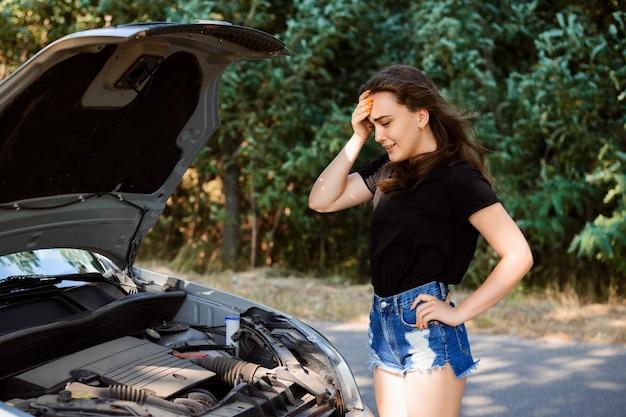 Mujer joven cerca de un capó abierto de un coche roto llora y no sabe qué hacer