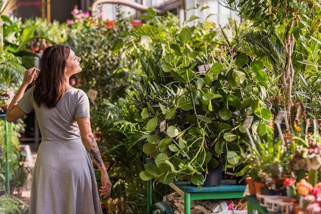 Mujer joven cerca de las plantas verdes en macetas