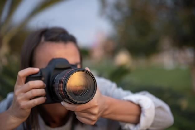 Mujer joven de cerca tomando fotografías al aire libre con una cámara slr profesional.