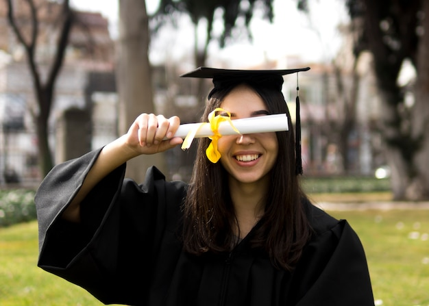 Mujer joven en la ceremonia de graduación cubriendo sus ojos con un diploma