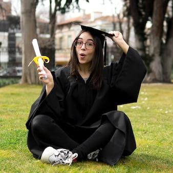 Mujer joven en la ceremonia de graduación sosteniendo su gorra