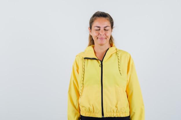 Mujer joven cerrando los ojos en un impermeable amarillo y mirando con recelo