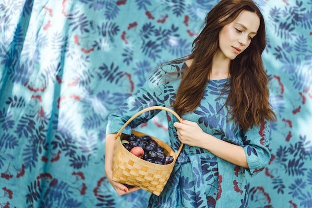 Mujer joven con una cesta de frutas, ciruelas y manzanas.