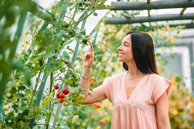 Mujer joven con una cesta de vegetación y cebolla en el invernadero