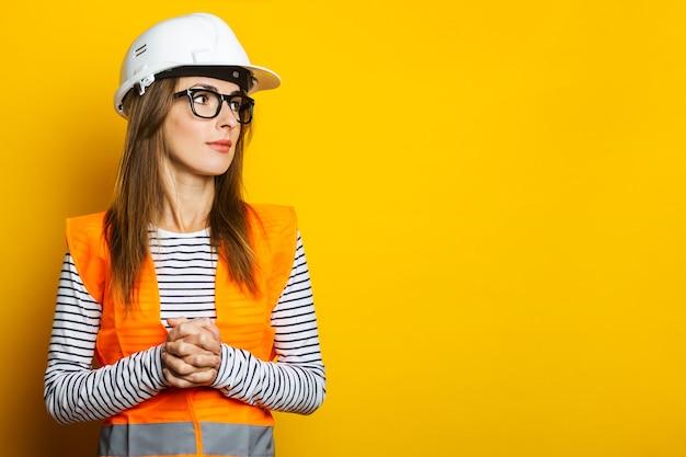 Mujer joven en un chaleco y casco en amarillo