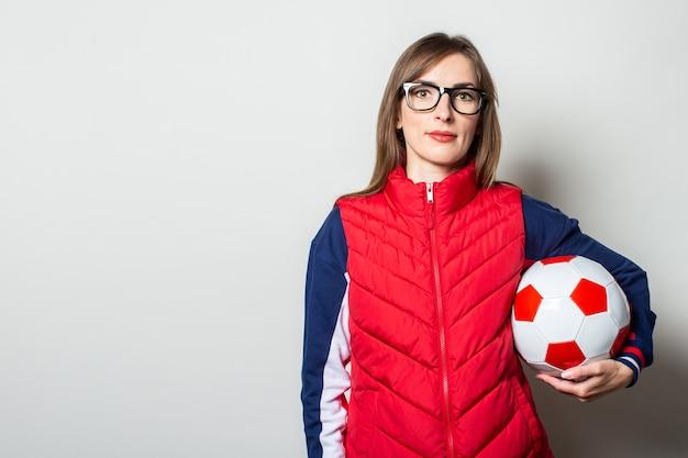Mujer joven en un chaleco rojo sosteniendo un balón de fútbol contra una pared de luz