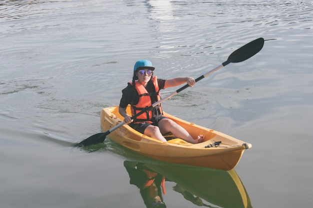 Mujer joven en los chalecos salvavidas anaranjados kayaking en un lago.