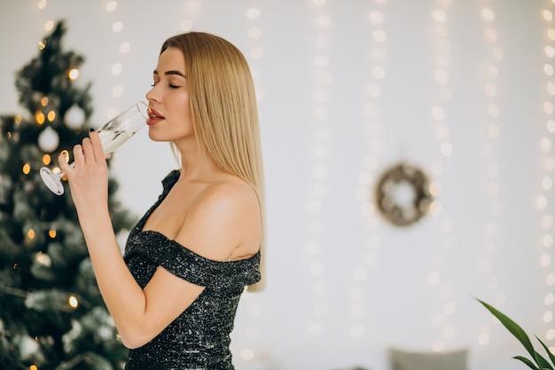 Mujer joven con champán por el árbol de navidad