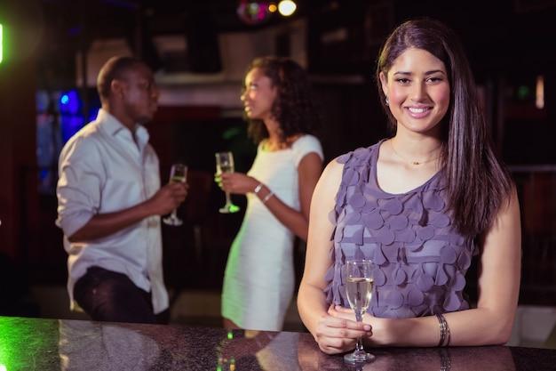 Mujer joven con champán en el bar mientras sus amigos se divierten