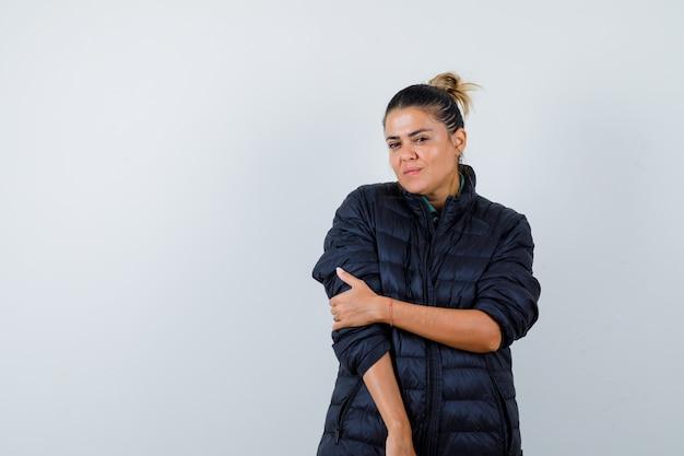 Mujer joven en chaqueta acolchada con la mano en el brazo y mirando confiado, vista frontal.