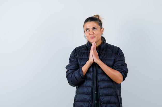 Mujer joven en chaqueta acolchada con las manos en gesto de oración, mirando hacia arriba y mirando soñadora, vista frontal.