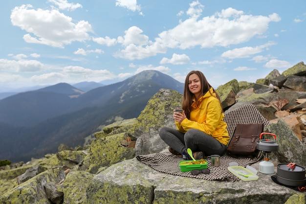 Mujer joven en chaqueta amarilla hacer un picnic en la cima de la montaña.