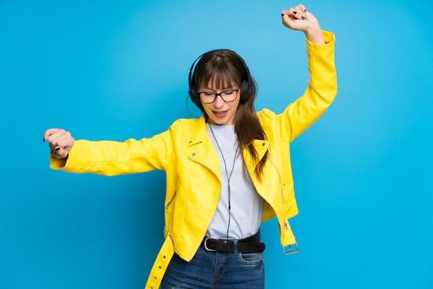 Mujer joven con chaqueta amarilla en la pared azul escuchando música con auriculares y bailando