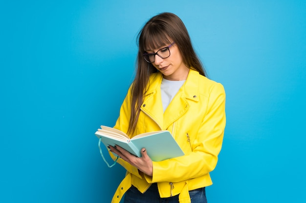Mujer joven con chaqueta amarilla en la pared azul sosteniendo un libro y disfrutando de la lectura