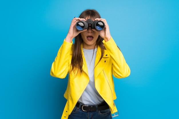 Mujer joven con chaqueta amarilla sobre fondo azul y mirando en la distancia con binoculares