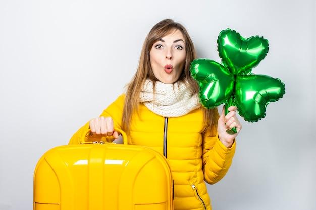 Mujer joven en una chaqueta amarilla y un sombrero aislado