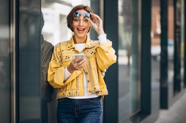 Mujer joven en chaqueta amarilla con teléfono afuera en la calle