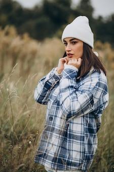 Mujer joven con chaqueta azul y sombrero blanco caminando en el bosque otoñal