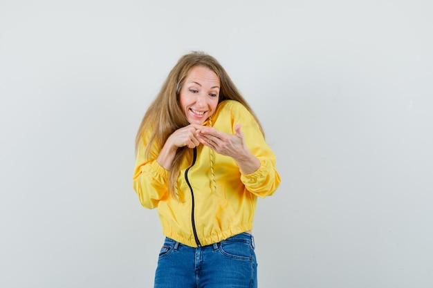 Mujer joven en chaqueta de bombardero amarilla y jean azul mirando las manos como sosteniendo algo imaginario y mirando optimista, vista frontal.