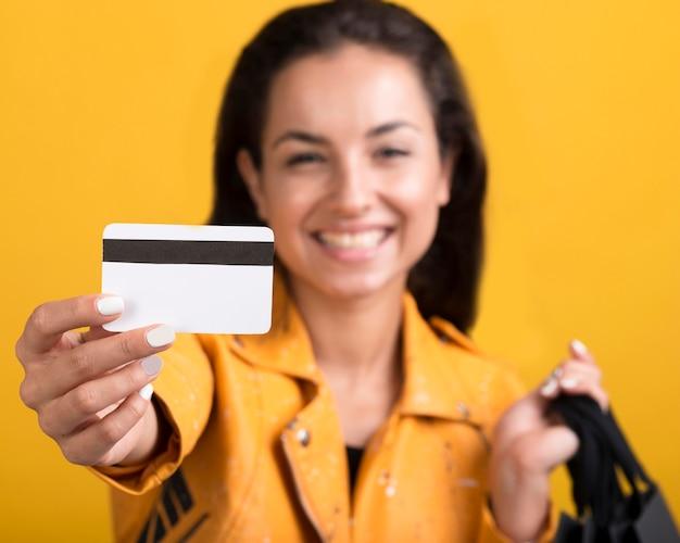 Mujer joven en chaqueta de cuero amarilla mostrando tarjeta de compras