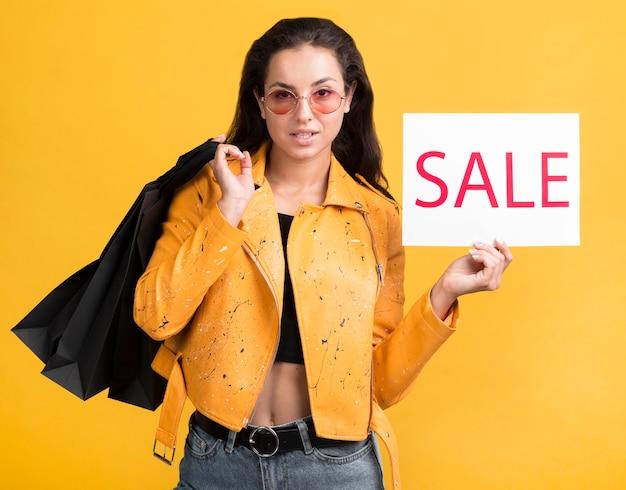 Mujer joven en chaqueta de cuero amarilla sosteniendo una pancarta de venta