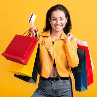 Mujer joven en chaqueta de cuero amarilla sosteniendo una tarjeta