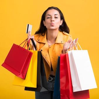 Mujer joven en chaqueta de cuero amarillo con bolsas de la compra.