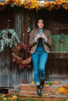 Mujer joven en una chaqueta marrón y jeans posa en una casa rústica