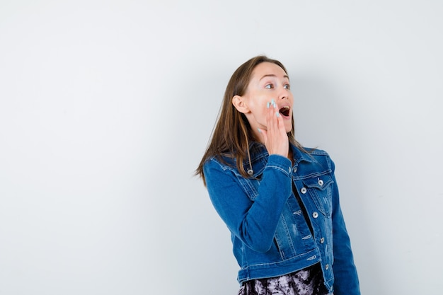 Mujer joven con chaqueta de mezclilla, vestido gritando manteniendo la mano cerca de la boca y mirando emocionado, vista frontal.