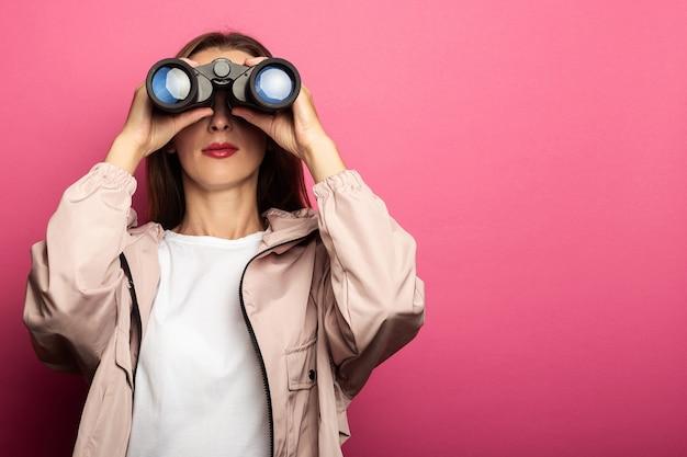 Mujer joven en chaqueta mirando a través de binoculares