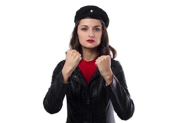 Mujer joven chaqueta negra, suéter rojo y sombrero con una referencia a ernesto che guevara mirando a puerta cerrada, demuestran sus puños sobre un fondo blanco.