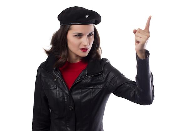 Mujer joven chaqueta negra, suéter rojo y sombrero con una referencia a ernesto che guevaraone mano levantada con el dedo índice sobre un fondo blanco.