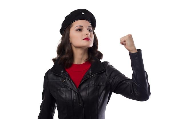 Mujer joven chaqueta negra, suéter rojo y sombrero con una referencia a ernesto che guevaraone mano levantada con puño sobre un fondo blanco.
