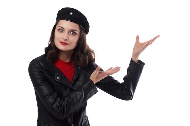 Mujer joven chaqueta negra, suéter rojo y sombrero con una referencia a ernesto che guevaraone manos levantadas con gesto de oferta comercial sobre un fondo blanco.