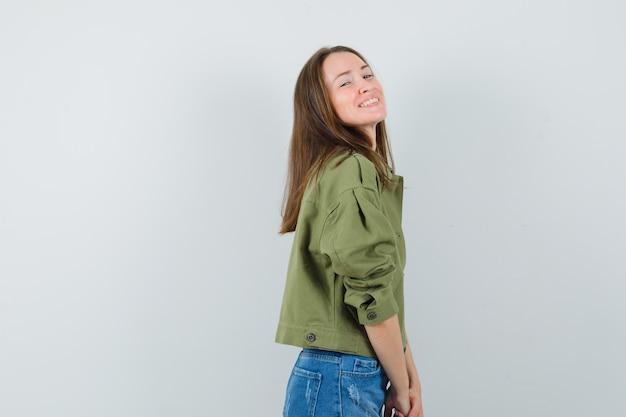 Mujer joven en chaqueta, pantalones cortos y mirando mareado. .