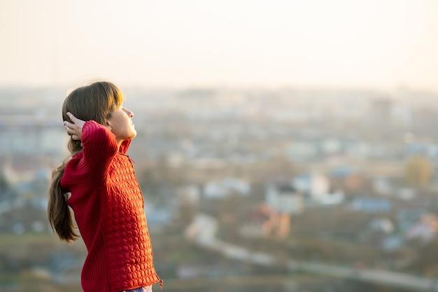 Mujer joven en chaqueta roja de pie con las manos detrás de la cabeza al aire libre disfrutando de la vista de la noche.